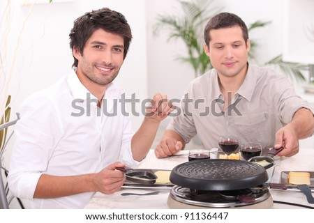 Men eating raclette - stock photo