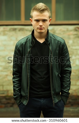 Men fashion concept. Portrait of a fashionable young man with stylish haircut wearing trendy leather jacket & posing over urban background. Perfect hair & skin. Hipster style. Outdoor shot - stock photo