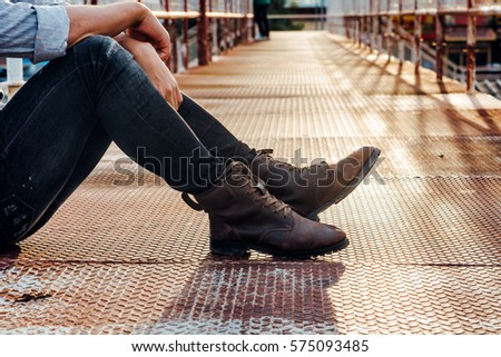 Men fashion in leather boots, Close up view on man's legs in black jeans and brown leather boots, Toned picture.