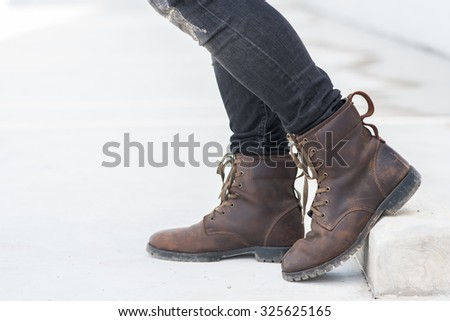 Men fashion legs in black jeans and brown leather boots on white - stock photo