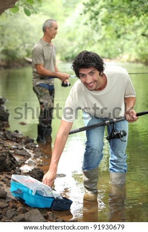 Men fishing in a river - stock photo