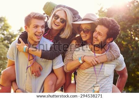 Men Giving Woman Piggybacks On Their Way To Music Festival - stock photo