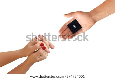 Men hand gives gift with engagement ring to female hand isolated.