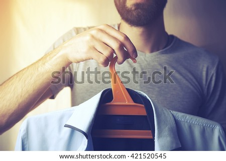 men hand holding hanger with t-shirt - stock photo
