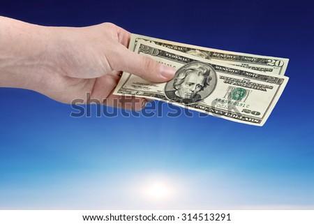 Men hand offer money over blue sky - stock photo