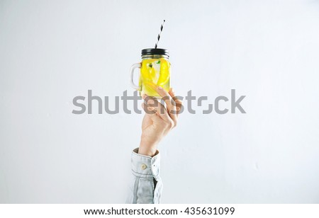 Men hand presents homemade cold lemonade from citrus lemon, sparkling water and ice cubes isolated on white. Refreshment healthy cold drink in summer time - stock photo