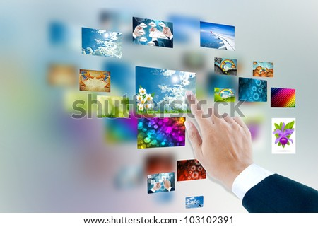 men hand using touch screen interface with pictures in frames - stock photo