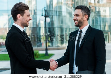 Men handshaking. Two confident young businessmen shaking hands and smiling while standing outdoors