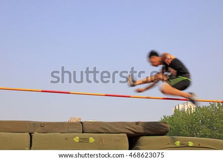 men high jump athletes in the playground