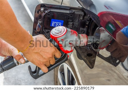 Men hold Fuel nozzle to add fuel in car at gas station - stock photo