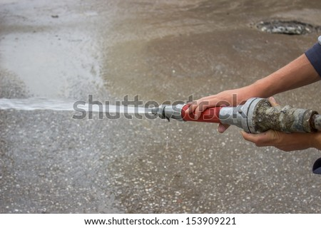 Men holding fire hose and spray water during street cleaning - stock photo