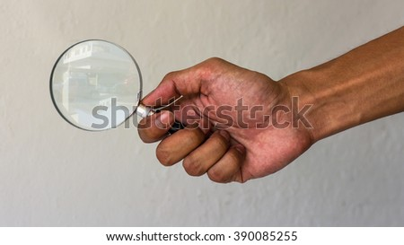 Men holding hands clutching the handle of a magnifying glass under the concrete buildings. - stock photo