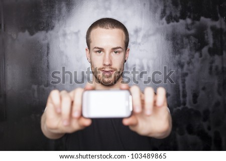 Men holding smartphone in hands and showing display, black t-shirt and background, studio shot - stock photo