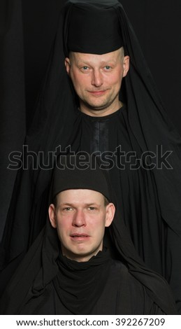 Men in a monk robe on a black background. - stock photo