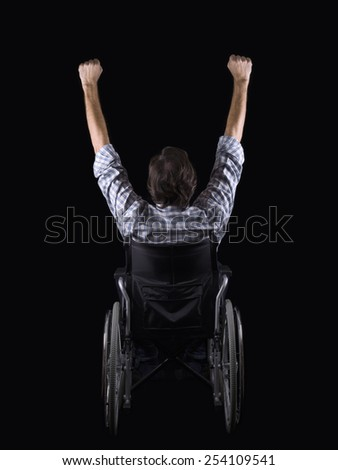 Men in a wheelchair,of backs and with the arms raised - stock photo