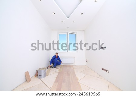 Men in blue overalls laid parquet in white room - stock photo