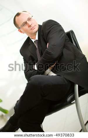 Men in glasses in suit on chair - stock photo