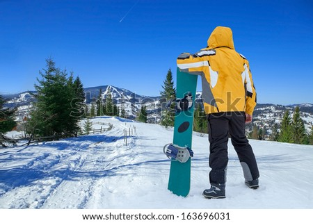 Men in goggles stay with snowboard on the top of mountain - stock photo