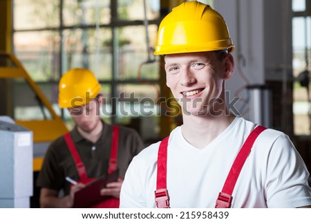 Men in hardhats during work at factory - stock photo