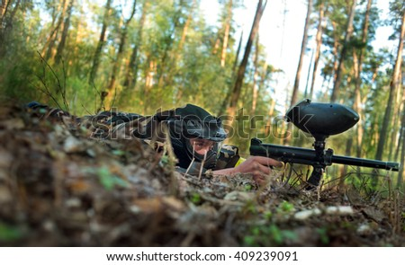 Men in protective suits and masks play paintball in the woods in summer - stock photo
