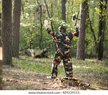 Men in protective suits and masks play paintball in the woods in summer. The soldier raised his hands and surrender shall - stock photo