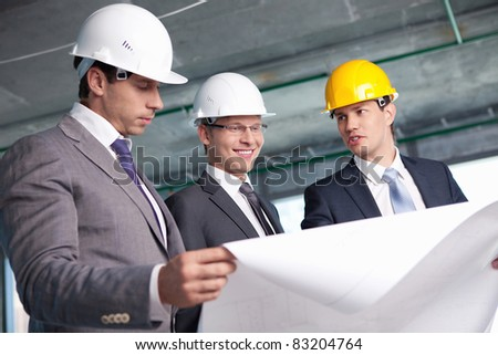 Men in suits at a construction site - stock photo
