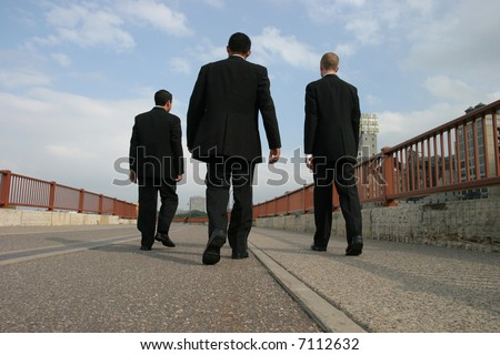 Men in Suits walking across bridge