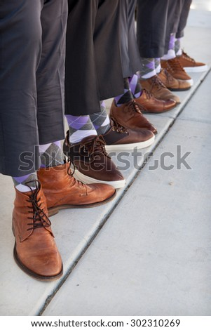 men in tan and brown shoes with purple argyle socks - stock photo