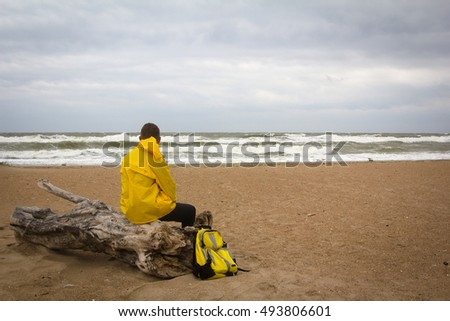 Men in yellow raincoat on the beach looking at storm.