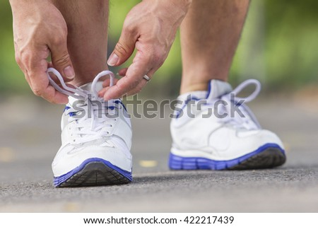 Men is tying shoes laces for jogging at park. sports healthy lifestyle concept focus on the right shoe. - stock photo