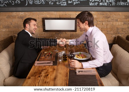 men laugh together while sitting in cafe. two man holding hands and greeting each other at table - stock photo