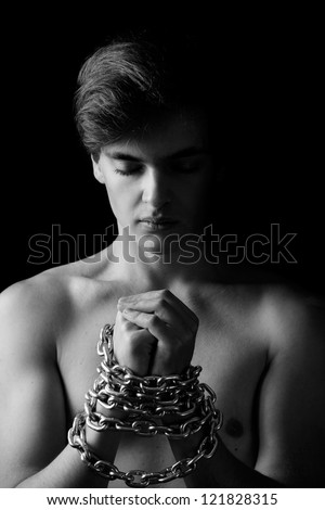 Men locked in metal chain on black background - stock photo