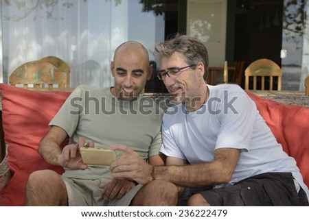 Men looking at photo or website on mobile phone - stock photo