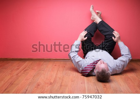 men lying in the floor on red wall background - stock photo