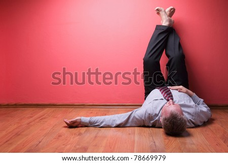 men lying in the floor on red wall background