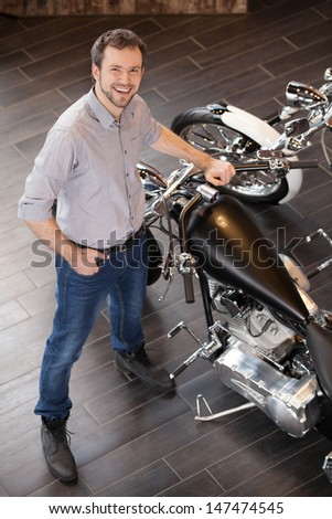 Men near motorcycle. Top view of cheerful young men standing near the motorcycle - stock photo