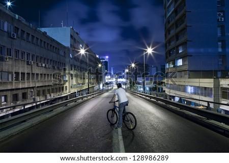 Men on a Bicycle - Dark street in Tel Aviv, Israel - stock photo
