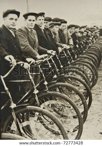 Men on bicycles, the beginning of the competition. Old photographs. - stock photo