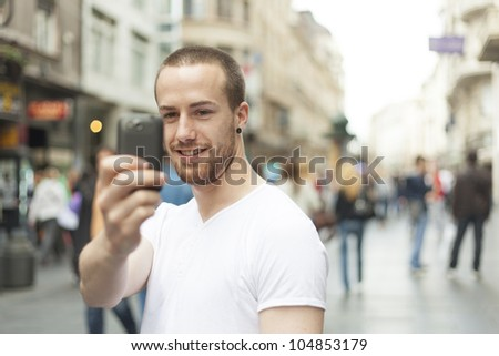 Men on street photographing with mobile phone, background is blured city - stock photo