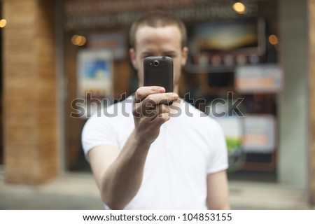 Men on street photographing with smartphone, background is blured city - stock photo