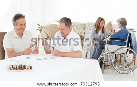 Men playing cards while their wives are talking - stock photo