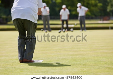 Men playing lawn bowls. Very narrow depth of field. Focus on player. - stock photo