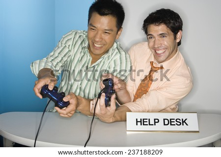 Men Playing Video Games at Help Desk - stock photo