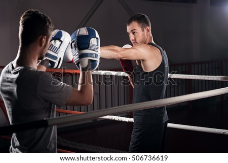 Men practicing boxing on ring