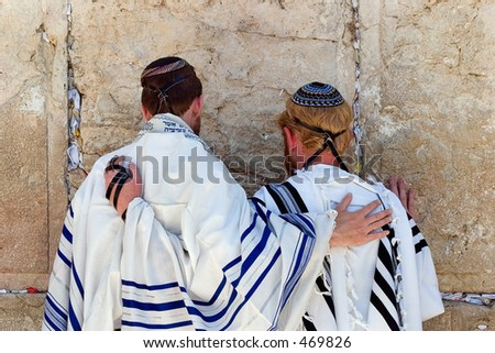 men praying at the wailing wall. - stock photo