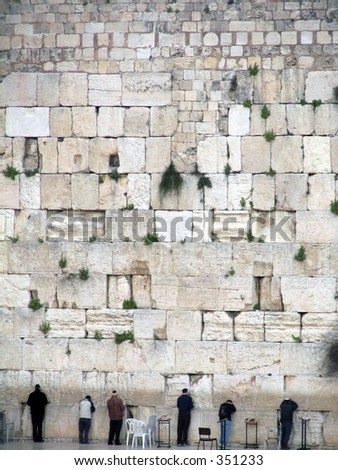 men praying at the western wall, the most holy site for the Jewish Culture. - stock photo