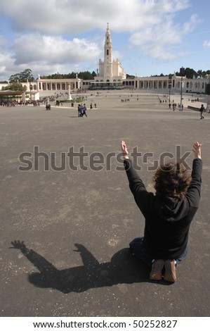 Men praying with Fatima (Portugal) temple as background - stock photo