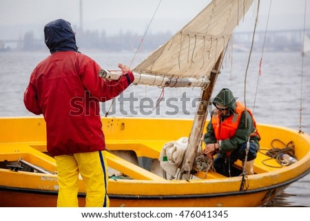 Men preparing their boat to sail away in the storm.