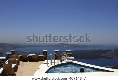 Men relaxing in a Jacuzzi on a dream house set on a hill overlooking the sea. - stock photo