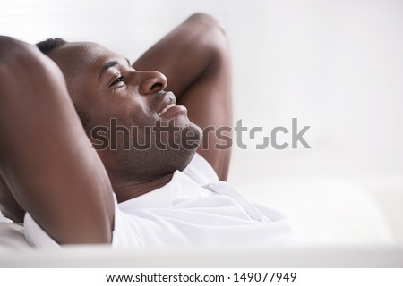 Men resting. Side view of happy African descent men sitting with his head in hands - stock photo